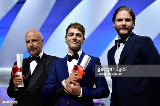 Director Xavier Dolan and producer Alain Sarde pose with actor Daniel Bruhl after being awarded with the Jury Prize for 'Mommy' and 'Adieu au...