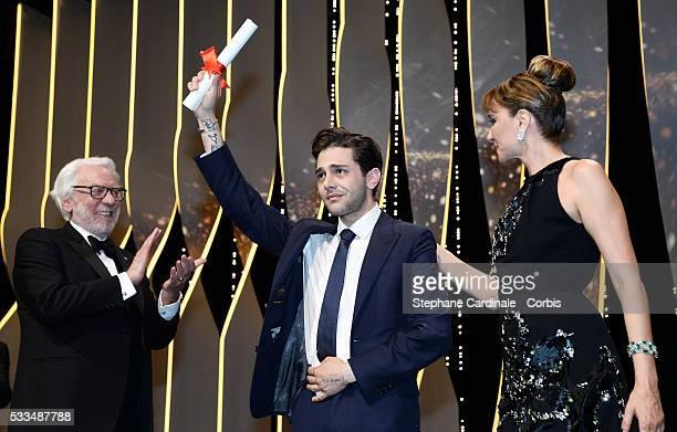 Director Xavier Dolan appears on stage with jury members Donald Sutherland and Valeria Golino after being awarded with the Grand Prix for the film...