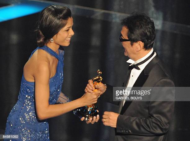 Director Yojiro Takita receives the trophy for Best Foreign Language Film of the Year from 'Slumdog Millionaire' supporting actress Freida Pinto at...