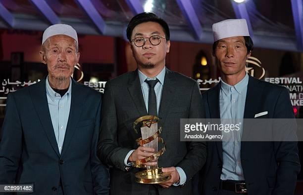 Director Zijian Wang poses with his award with Chinese actor Yang Shengcang and his son Yang Shengcang during the closing ceremony of the 16th...