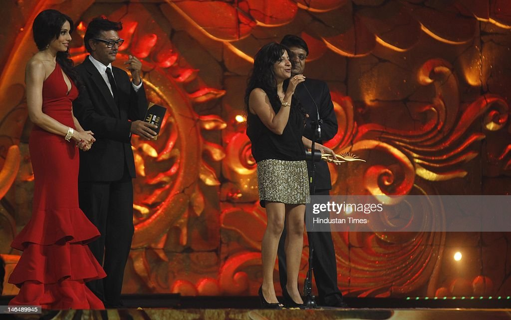 Director Zoya Akhtar receiving best director award while actor Bipasha Basu standing on the left side of stage at 13th International India Film...