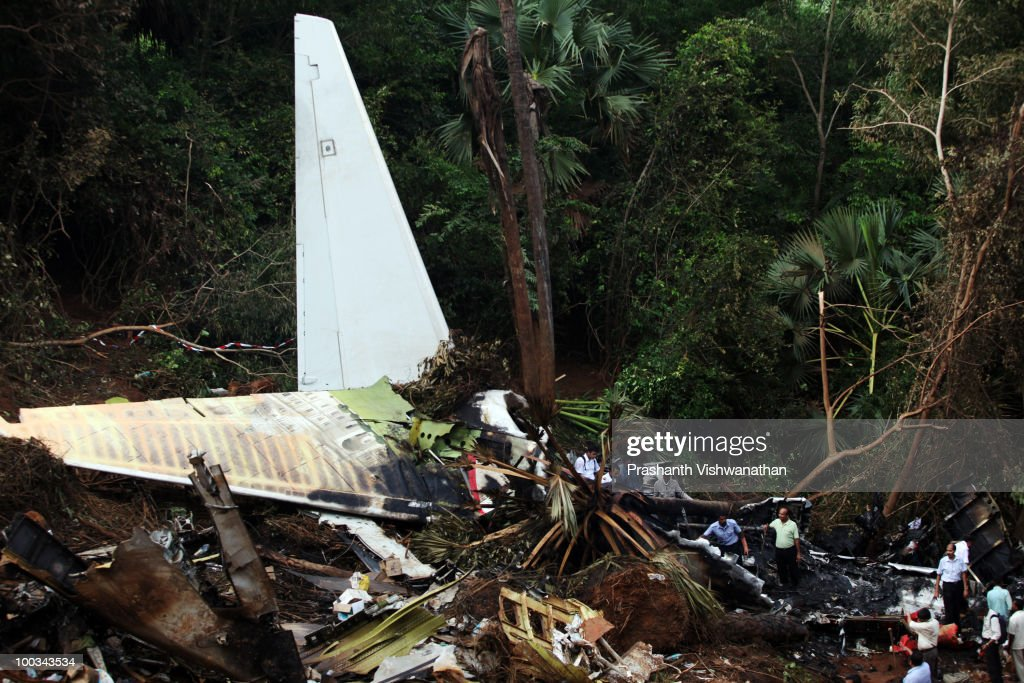 Directorate General Civil Aviation (DGCA) officers inspect the plane crash site on May 23, 2010 in Mangalore. An Air India Express Boeing 737-800 series aircraft arriving from Dubai, with 166 people onboard, overshot the runway on landing in Mangalore and crashed into a forest. Airline officials say 8 survivors have been rescued with 158 others feared dead.