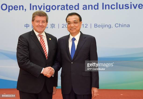 Director-General Guy Ryder of the International Labor Organization shakes hands with Chinese Premier Li Keqiang before The 1+6 Round Table Dialogue...