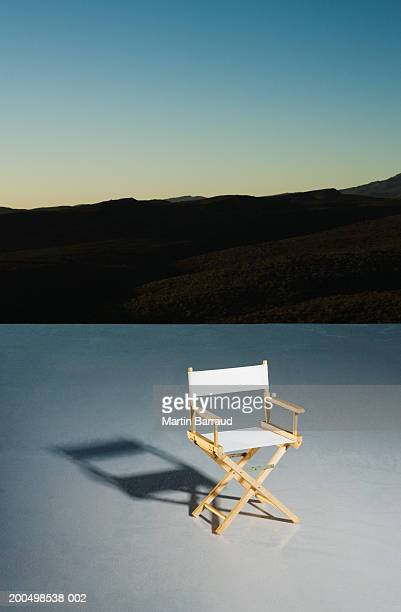 Director's chair on platform at down, mountains in background