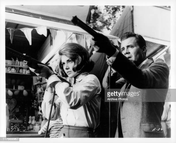 Dirk Bogarde and Sylva Koscina holding rifles in a scene from the film 'Agent 8 3/4' 1964