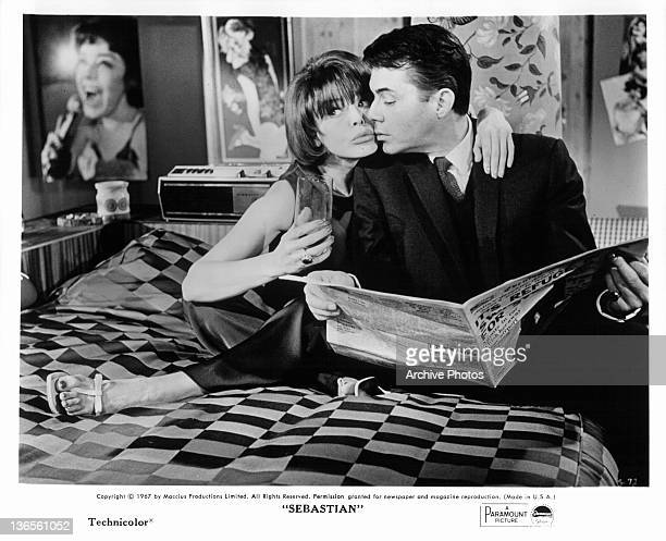 Dirk Bogarde sitting on a bed reading the newspaper with an Janet Munro in a scene from the film 'Sebastian' 1968