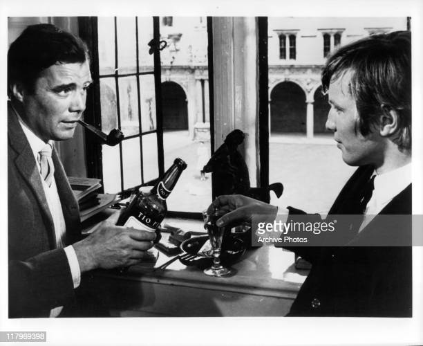Dirk Bogarde smoking a cigar while holding a bottle of Tio Pepe sherry to Michael York holding a glass of sherry in a scene from the film 'Accident'...