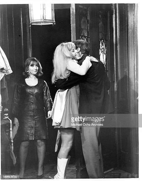 Dirk Bogarde welcomes Edina Ronay and her friend to his party in a scene from the film 'Our Mother's House' 1967