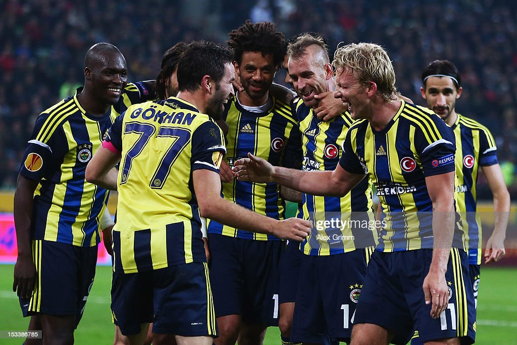 Dirk Kuyt of Fenerbahce celebrates his team's third goal with team mate Goekhan Goenuel and others during the UEFA Europa League group C match between Borussia Moenchengladbach and Fenerbahce SK at Borussia-Park on October 4, 2012 in Moenchengladbach, Germany.