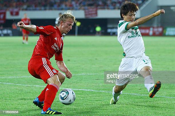 Dirk Kuyt of Liverpool challenges Shi Liang of Guangdong Sunray Cave during the preseason friendly match between Guangdong Sunray Cave and Liverpool...