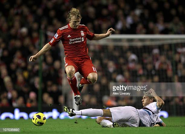 Dirk Kuyt of Liverpool hurdles the tackle of Radoslav Kovac of West Ham United during the Barclays Premier League match between Liverpool and West...