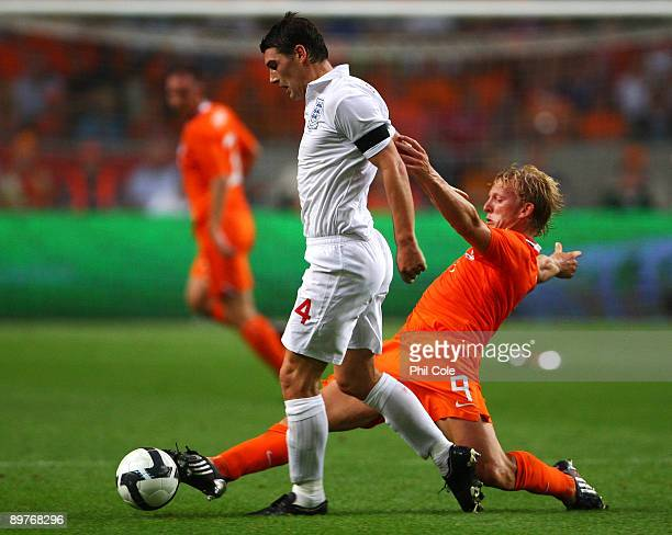 Dirk Kuyt of Netherlands tackles Gareth Barry of England during the International Friendly between Netherlands and England at the Amsterdam Arena on...