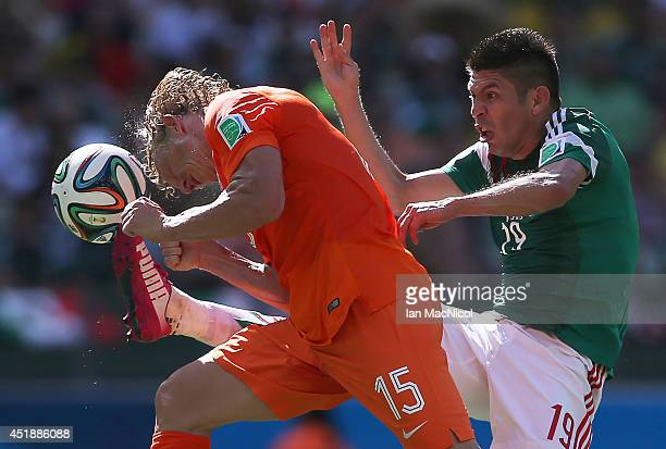 Dirk Kuyt of Netherlands vies with Oribe Peralta of Mexico during the Round of 16 match of the 2014 World Cup between Netherlands and Mexico at the...