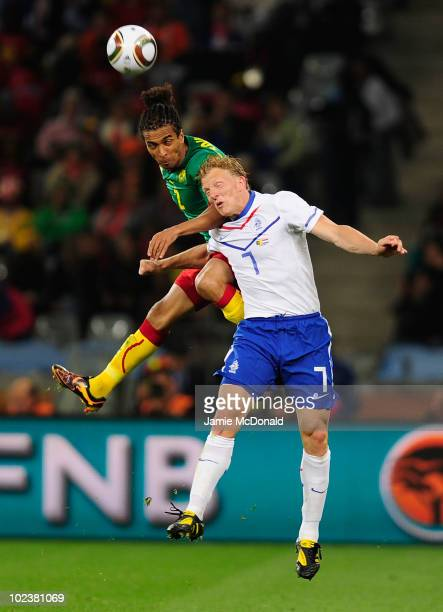 Dirk Kuyt of the Netherlands and Benoit AssouEkotto of Cameroon jump for the ball during the 2010 FIFA World Cup South Africa Group E match between...