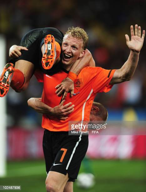 Dirk Kuyt of the Netherlands carries goalscorer Wesley Sneijder after he scores his side's second goal during the 2010 FIFA World Cup South Africa...