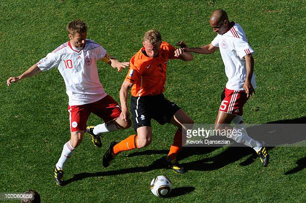 Dirk Kuyt of the Netherlands is challenged by Martin Jorgensen and Simon Poulsen of Denmark during the 2010 FIFA World Cup Group E match between...