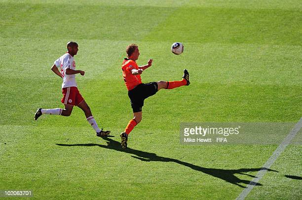Dirk Kuyt of the Netherlands is chased by Simon Poulsen of Denmark during the 2010 FIFA World Cup Group E match between Netherlands and Denmark at...