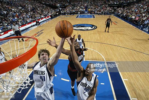 Dirk Nowitzki and Alan Henderson of the Dallas Mavericks shoot against the Philadelphia 76ers on January 29 2005 at the American Airlines Center in...