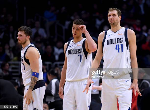 Dirk Nowitzki Dwight Powell and Luka Doncic of the Dallas Mavericks look on during a 121112 LA Clipper win at Staples Center on February 25 2019 in...