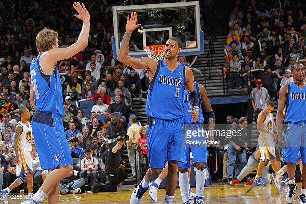 Dirk Nowitzki highfives Tyson Chandler of the Dallas Mavericks after a made shot against the Golden State Warriors on March 16 2011 at Oracle Arena...