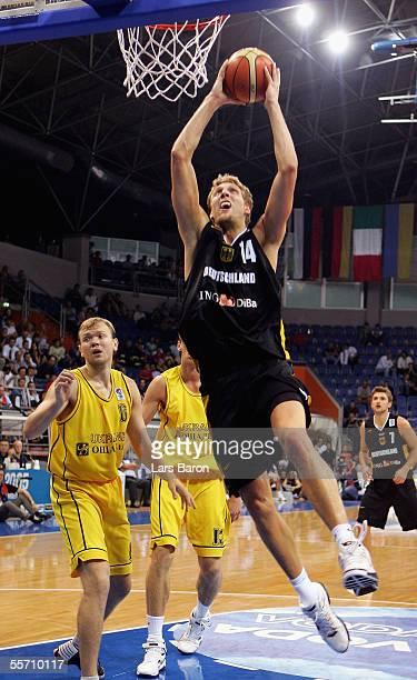 Dirk Nowitzki of Germany in action with Viktor Kobzystyy and Oleksiy Pecherov of Ukraine during the FIBA EuroBasket 2005 match between Ukraine and...