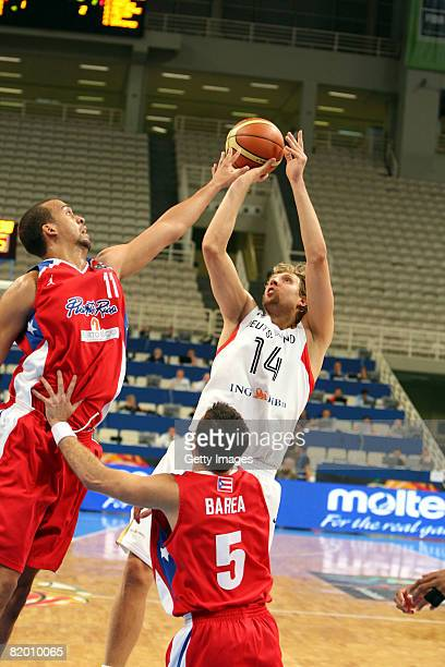 Dirk Nowitzki of Germany shoots against Ricardo Sanchez of Puerto Rico compete during the Fiba Olympic Qualifier match between Germany and Puerto...