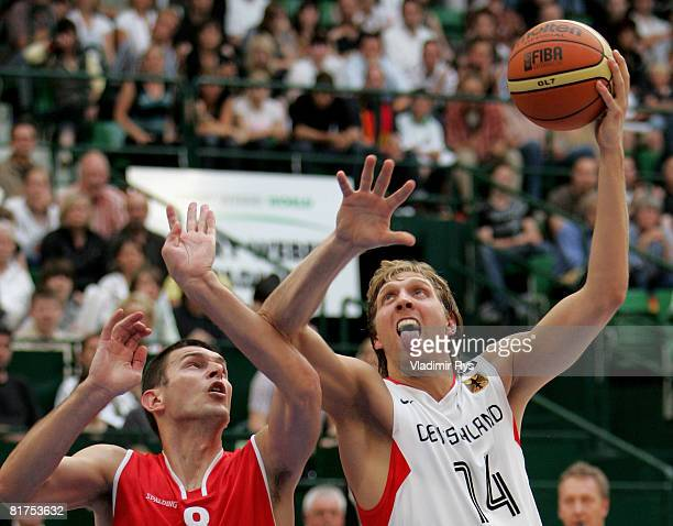 Dirk Nowitzki of Germany shoots as Filip Dylewicz of Poland defends during the international friendly basketball match between Germany and Poland at...