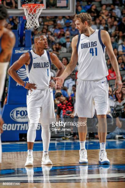 Dirk Nowitzki of the Dallas Mavericks and Dennis Smith Jr #1 of the Dallas Mavericks react during a preseason game against the Orlando Magic on...