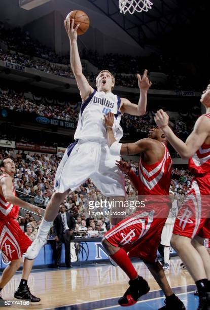 Dirk Nowitzki of the Dallas Mavericks attempts to shoot over Tracy McGrady of the Houston Rockets in Game seven of the Western Conference...