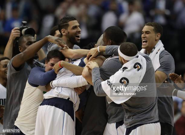 Dirk Nowitzki of the Dallas Mavericks celebrates after scoring his 30000 career point with Mark Cuban and his team in the second quarter against the...