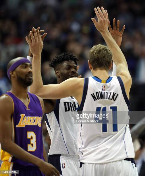 Dirk Nowitzki of the Dallas Mavericks celebrates after scoring his 30000 career point with Nerlens Noel in the second quarter against the Los Angeles...