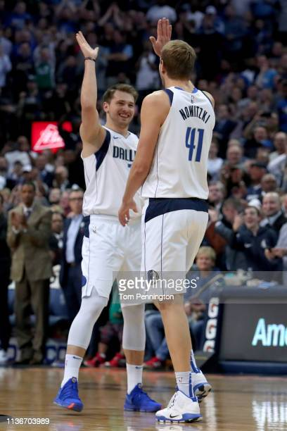 Dirk Nowitzki of the Dallas Mavericks celebrates with Luka Doncic of the Dallas Mavericks after scoring a basket against Kenrich Williams of the New...