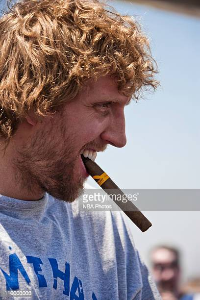 Dirk Nowitzki of the Dallas Mavericks chews on a victory cigar as the Mavs are greeted by thousands of fans after winning the 2010 - 2011 NBA...