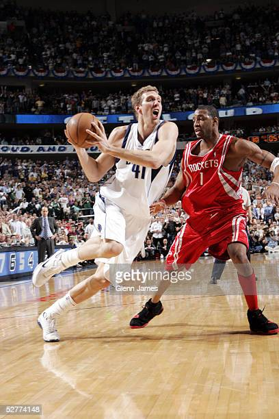 Dirk Nowitzki of the Dallas Mavericks drives past Tracy McGrady of the Houston Rockets in Game seven of the Western Conference Quarterfinals during...