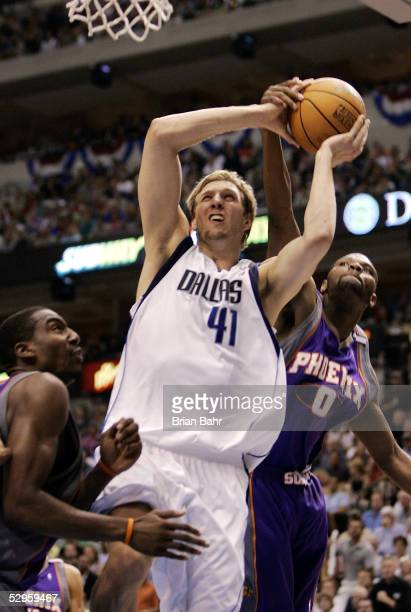Dirk Nowitzki of the Dallas Mavericks gets fouled by Walter McCarty of the Phoenix Suns but isn't awarded a free throw on the penalty in the second...