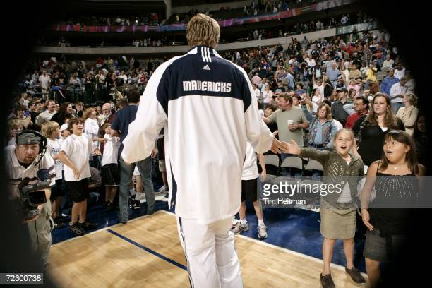 Dirk Nowitzki of the Dallas Mavericks gives a highfive to a young fan during the preseason game against the Washington Wizards on October 21 2006 at...