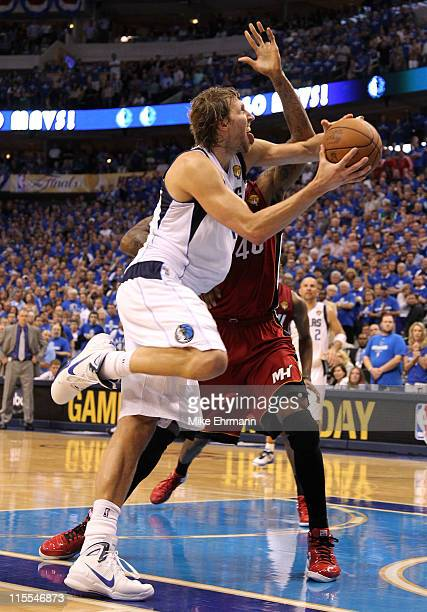 Dirk Nowitzki of the Dallas Mavericks goes up for a shot against Udonis Haslem of the Miami Heat with 14 seconds remaining and scores to put the...