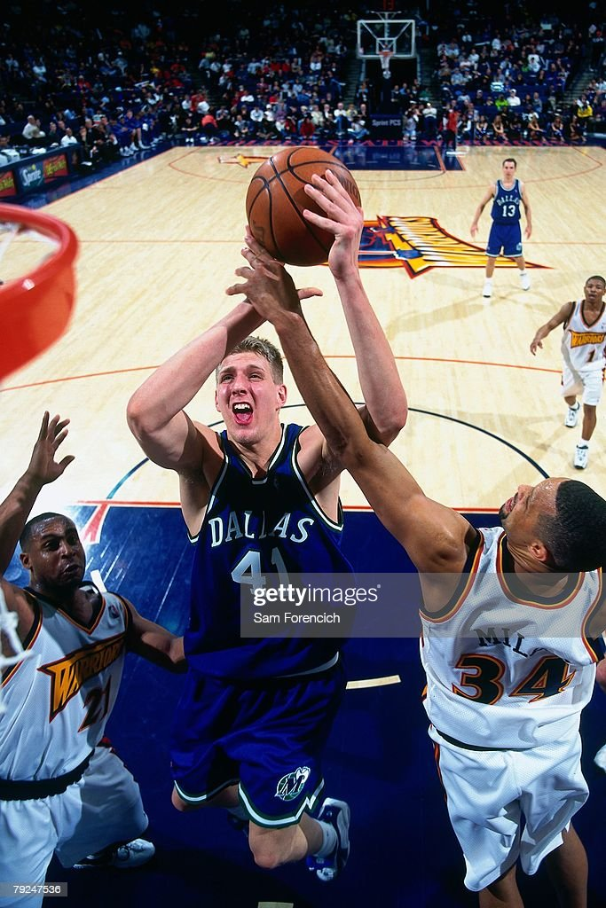 Dirk Nowitzki #41 of the Dallas Mavericks goes up for a shot against Chris Mills #34 of the Golden State Warriors during the game at the Arena in Oakland on February 7, 1999 in Oakland, California.