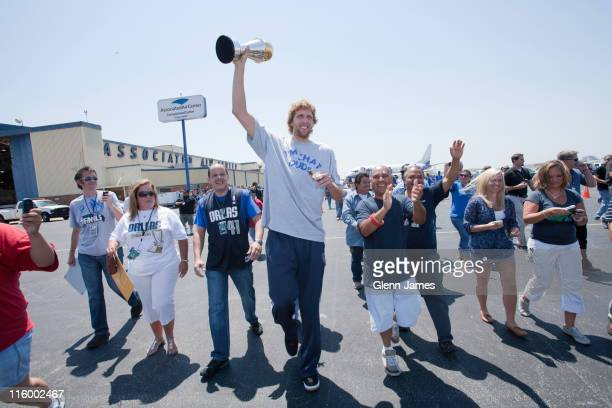 Dirk Nowitzki of the Dallas Mavericks hoists his Bill Russell NBA Finals MVP trophy as the Mavs are greeted by thousands of fans after winning the...