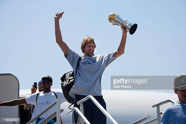 Dirk Nowitzki of the Dallas Mavericks hoists his Bill Russell NBA Finals MVP trophy as the team is greeted by thousands of fans after winning the...