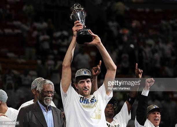 Dirk Nowitzki of the Dallas Mavericks holds up the Bill Russell Finals MVP trophy after Bill Russell presented it to him following the Mavericks...