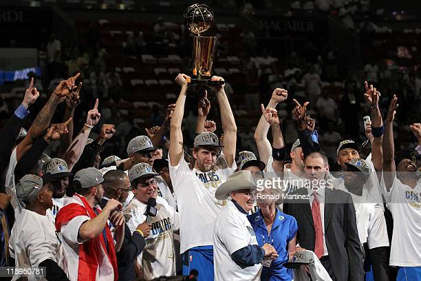 Dirk Nowitzki of the Dallas Mavericks holds up the Larry O'Brien trophy as he celebrates with his teammates and team owner Mark Cuban aftre the...