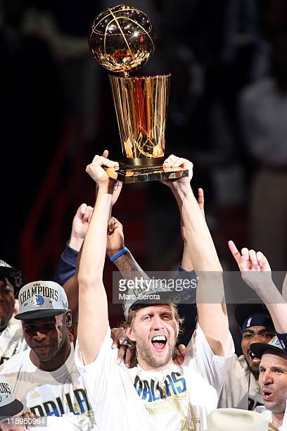 Dirk Nowitzki of the Dallas Mavericks holds up the Larry O'Brien trophy as he celebrates with Brendan Haywood and other teammates after the Mavericks...