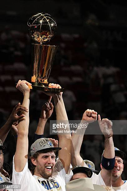 Dirk Nowitzki of the Dallas Mavericks holds up the Larry O'Brien Championship trophy after the Mavericks won 10595 against the Miami Heat in Game Six...