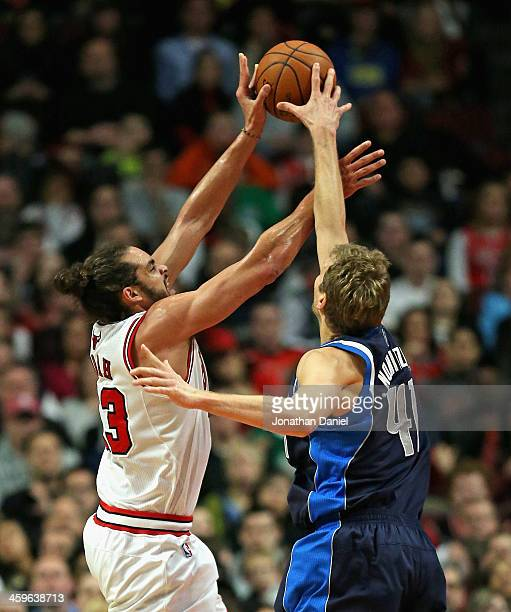 Dirk Nowitzki of the Dallas Mavericks knocks the ball away from Joakim Noah of the Chicago Bulls at the United Center on December 28 2013 in Chicago...