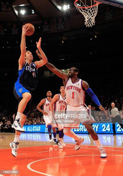 Dirk Nowitzki of the Dallas Mavericks lays the ball up over Amare Stoudemire of the New York Knicks at Madison Square Garden on February 19 2012 in...
