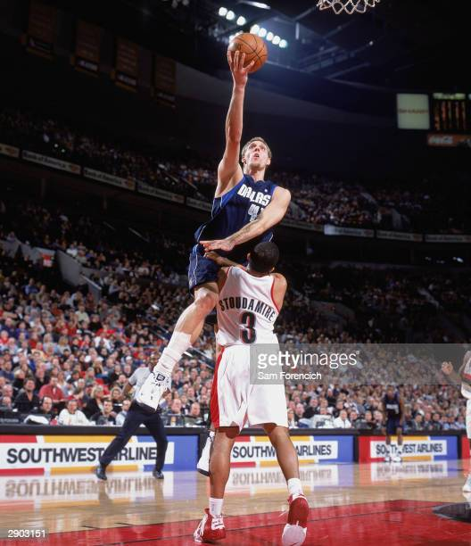 Dirk Nowitzki of the Dallas Mavericks lays up a shot against Damon Stoudamire of the Portland Trail Blazers during the game on January 17 2004 at the...
