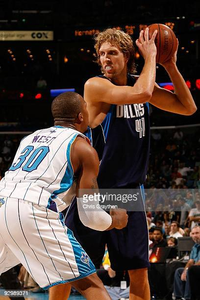 Dirk Nowitzki of the Dallas Mavericks looks to make a shot around David West of the New Orleans Hornets at New Orleans Arena on November 4 2009 in...