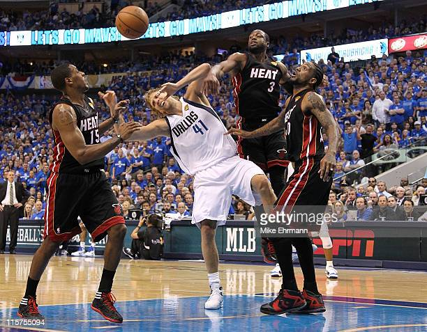 Dirk Nowitzki of the Dallas Mavericks loses the ball as he drives against Mario Chalmers Dwyae Wade and Udonis Haslem of the Miami Heat in the second...