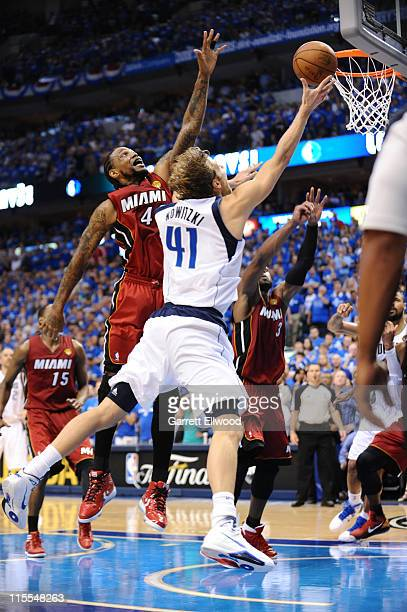 Dirk Nowitzki of the Dallas Mavericks makes a layup against Udonis Haslem of the Miami Heat with 149 seconds remaining in regulation during Game Four...
